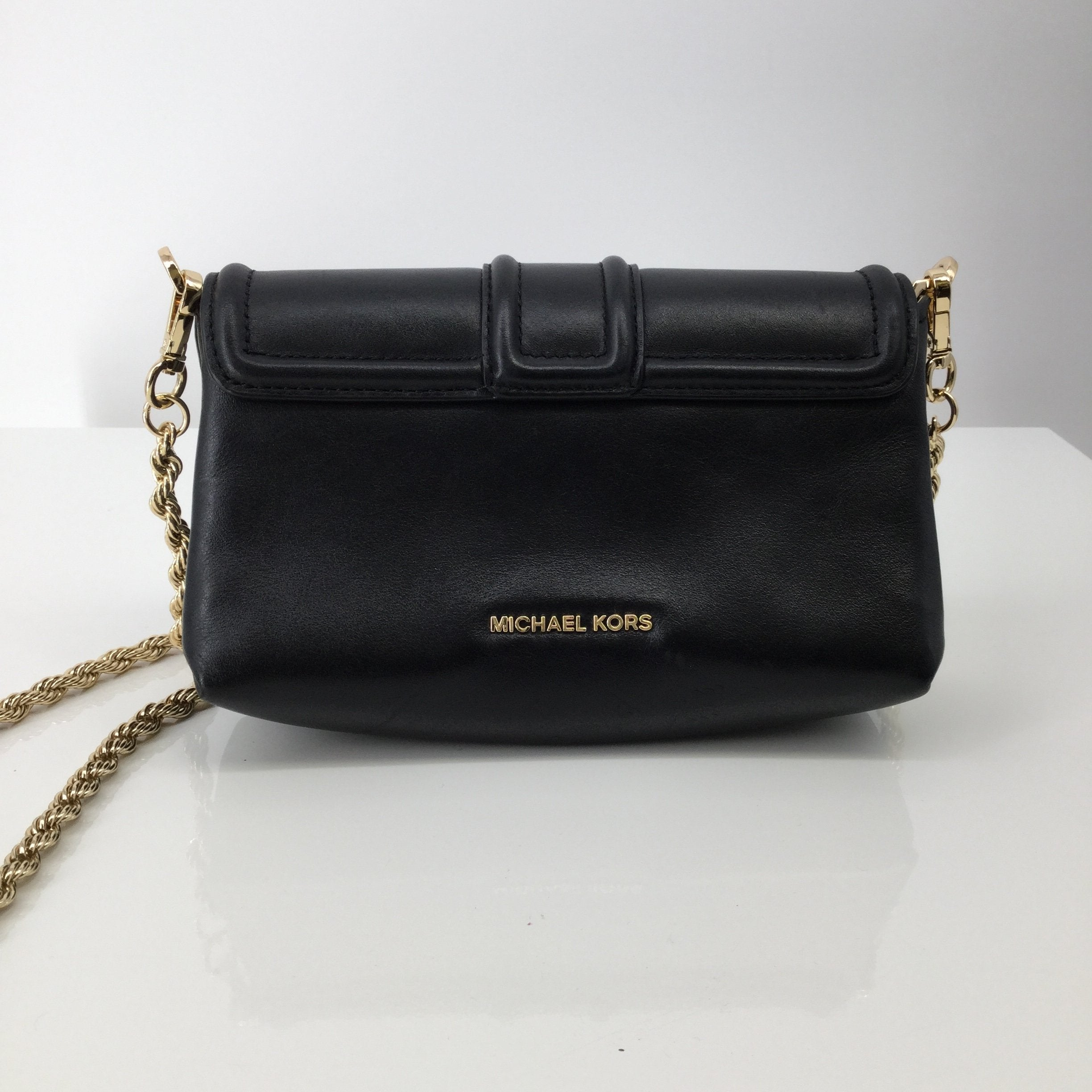 Michael Kors Designer Handbag, Leather, Black, Size: Small - <P>THIS MICHAEL KORS CROSSBODY FEATURES A GOLD CHAIN STRAP AND A GOLD LOCK ON THE FRONT. THE BAG CLOSES WITH A MAGNET. THIS CUTE CROSSBODY DOES COME WITH A BIT OF WEAR. THERE ARE SOME MINOR SCRATCHES ON THE BACK NEAR THE BOTTOM (SEE PHOTOS).</P>
