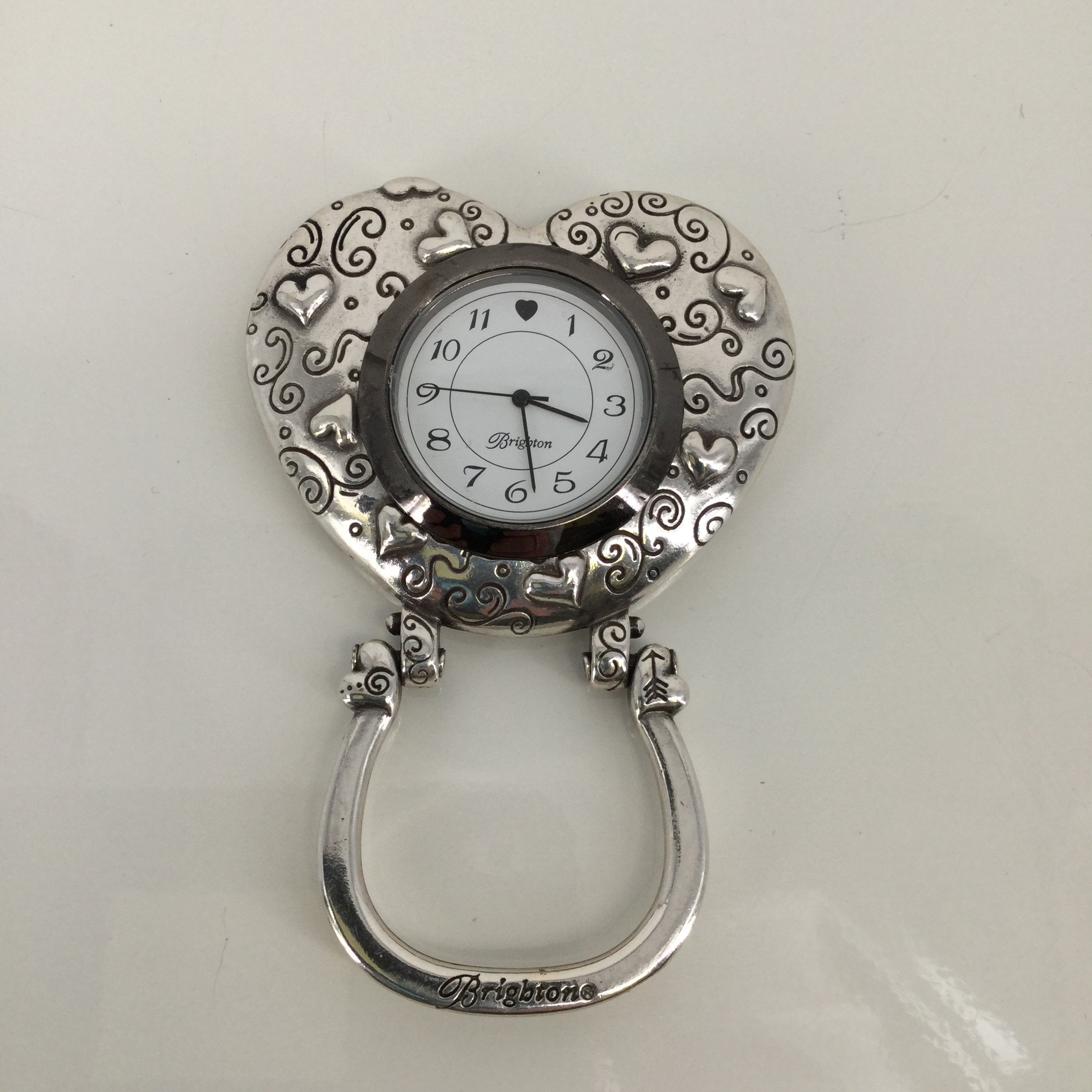Brighton Silver Watch - <P>THIS WATCH FROM BRIGHTON IS HEART SHAPED. IT IS SILVER WITH A HEART PATTERN. IT HAS AN ADJUSTABLE STAND ATTACHED TO IT. THIS WATCH IS IN VERY GOOD CONDITION!</P>