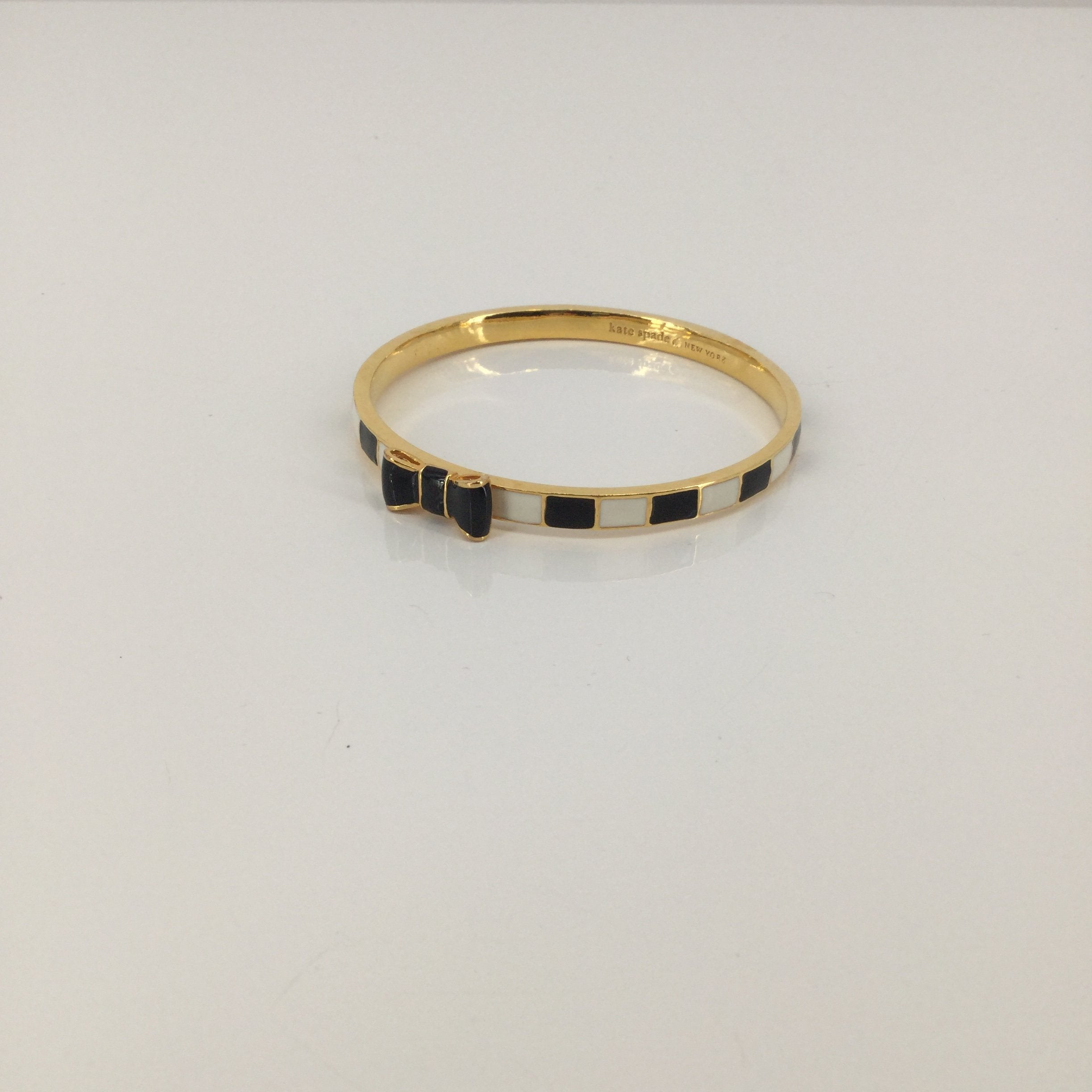 Kate Spade Gold, White, And Black Bracelet - <P>THIS KATE SPADE BRACELET IS GOLD WITH WHITE AND BLACK ON THE OUTSIDE. IT FEATURES A CUTE BOW IN THE FRONT. THIS BRACELET SLIPS ON OVER YOUR HAND. IT IS IN VERY GOOD CONDITION WITH SOME MINOR WEAR (SEE PHOTOS).</P>
