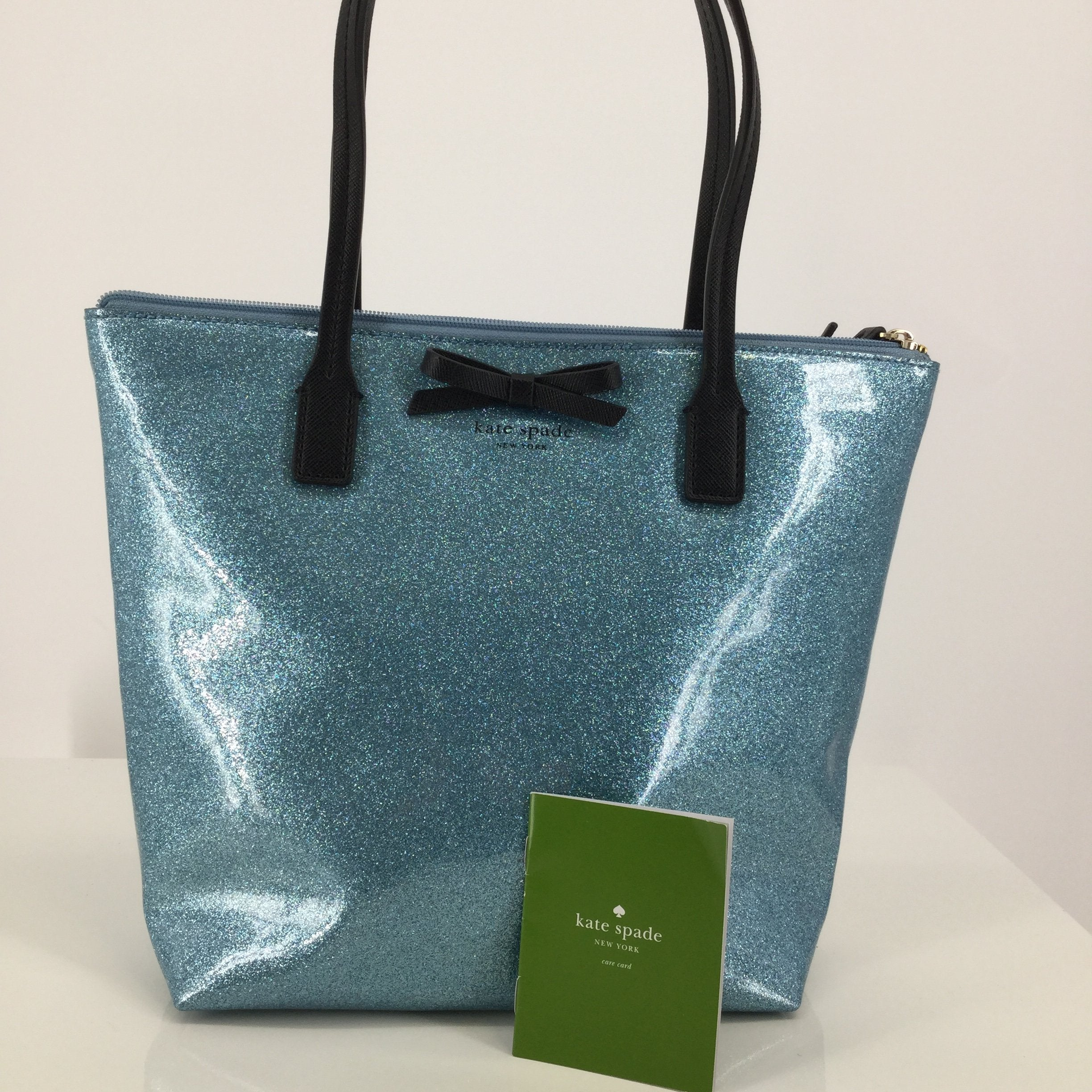 Kate Spade Blue Glitter Designer Handbag - <P>THIS SPARKLY KATE SPADE IS ADORABLE! IT IS LIGHT BLUE WITH BLACK STRAPS AND A BLACK BOW ON THE FRONT. INSIDE, THERE IS A ZIPPER POCKET AND TWO SLIP POCKETS. THIS BAG IS IN PERFECT CONDITION AND LOOKS LIKE IT HAS NEVER BEEN USED!</P>