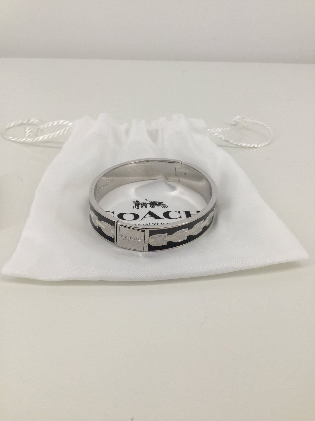 Coach Silver Bracelet - <P>THIS COACH BRACELET IS BEAUTIFUL! IT HAS A C PATTERN ON IT AND IT COMES WITH THE PROTECTIVE BAG. IT OPENS AND CLOSES TO PUT IT ON. THIS BRACELET IS IN EXCELLENT CONDITION WITH LITTLE TO NO SIGNS OF WEAR.</P>