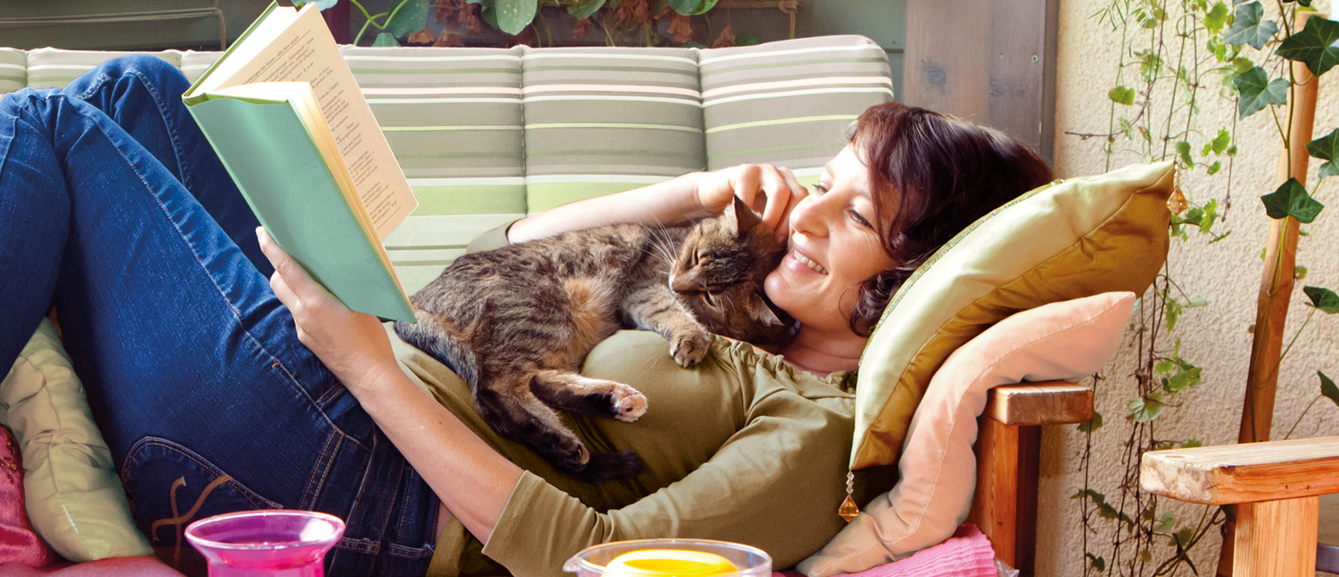 Women sharing a story with her contented and elderly cat on a comfy sofa
