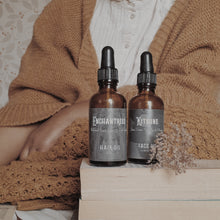 Load image into Gallery viewer, Image of Enchantress Hair Oil and Kitsune Face Oil on top of a stack of books, with a woman wearing a button up white shirt and a warm orange-brown jumper in the background.