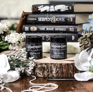 Heartrender and The Maiden Death body butters on sliced section of a tree, with a blurred stack of black books in the background and white flowers framing them in the foreground. Photo by Katrina at @acourtofbooksandcoffee on Instagram.