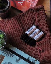 Load image into Gallery viewer, Photos of white label perfumes (Marzanna, Aceso and Hygeia) on top of a dark red-brown knit, with the edges of a journal and a succulent in the photo. Photo taken by Lauren from @blackcoffeebooks35