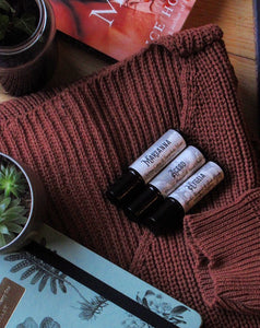 Photos of white label perfumes (Marzanna, Aceso and Hygeia) on top of a dark red-brown knit, with the edges of a journal and a succulent in the photo. Photo taken by Lauren from @blackcoffeebooks35