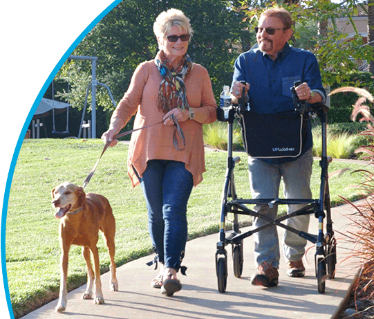 A man with a walker & woman with a dog take a park stroll beside text outlining UPWalker's fixed monthly financing options.