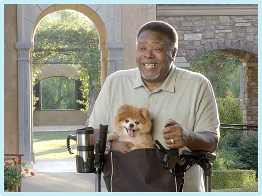 A smiling senior man excitedly reviews his UPWalker Upright Walker while his small dog sits in the walker's bag attachment.
