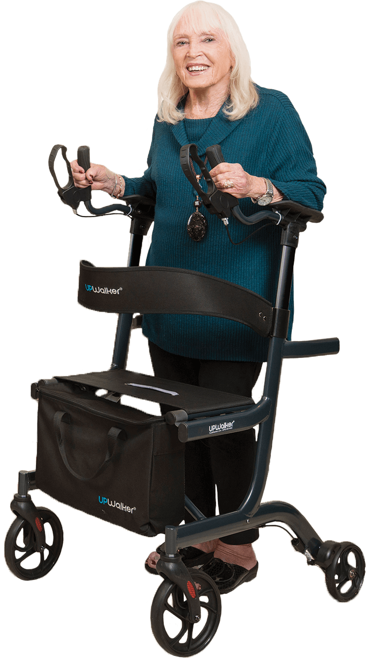 An elderly woman pushing an UPWalker rollator. The walker has several attachments, including a carry bag & backrest support.