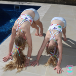girls doing downward dog pose by the pool in activewear
