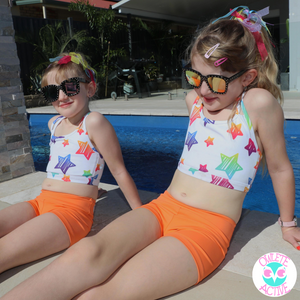 girls activewear bright orange shorts in a set with white crop top for girls at the pool