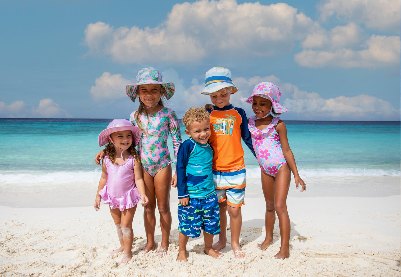 infant and toddlers posing for picture on top of pier at the beach wearing head to toe flap happy products.