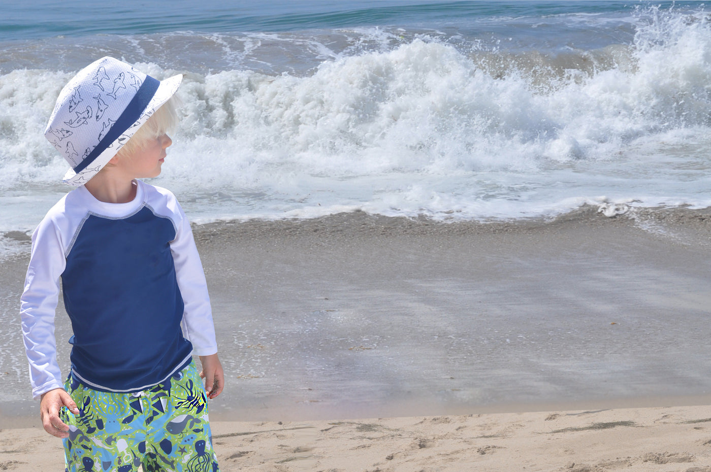 Young boy is standing at the beach in front of the ocean looking off to the right. Boy wearing matching white shark Flap Happy hat, blue and white long sleeve rash guard and green and blue crab print swim shorts.