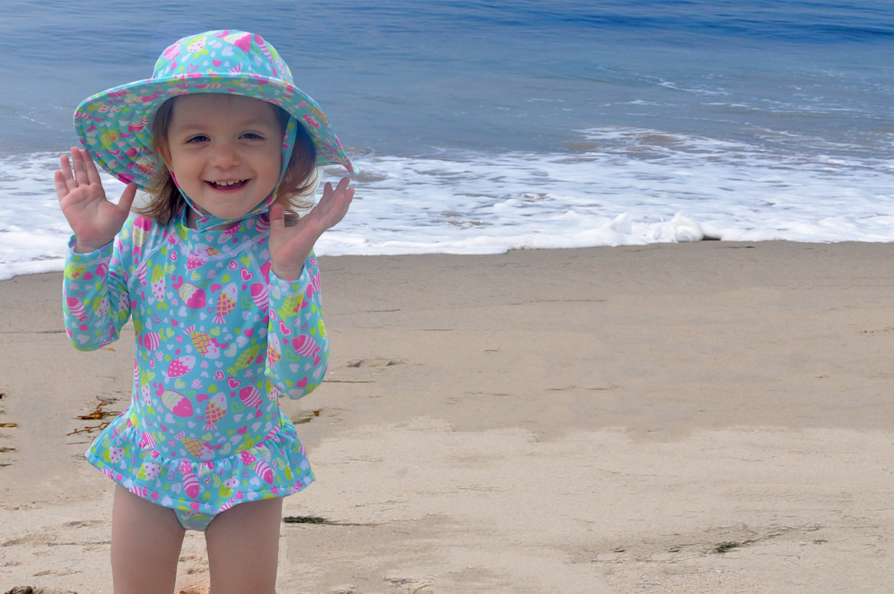 Young girl playing at the beach wearing the Flap Happy rainbow fish swimsuit and matching Flap Happy hat.