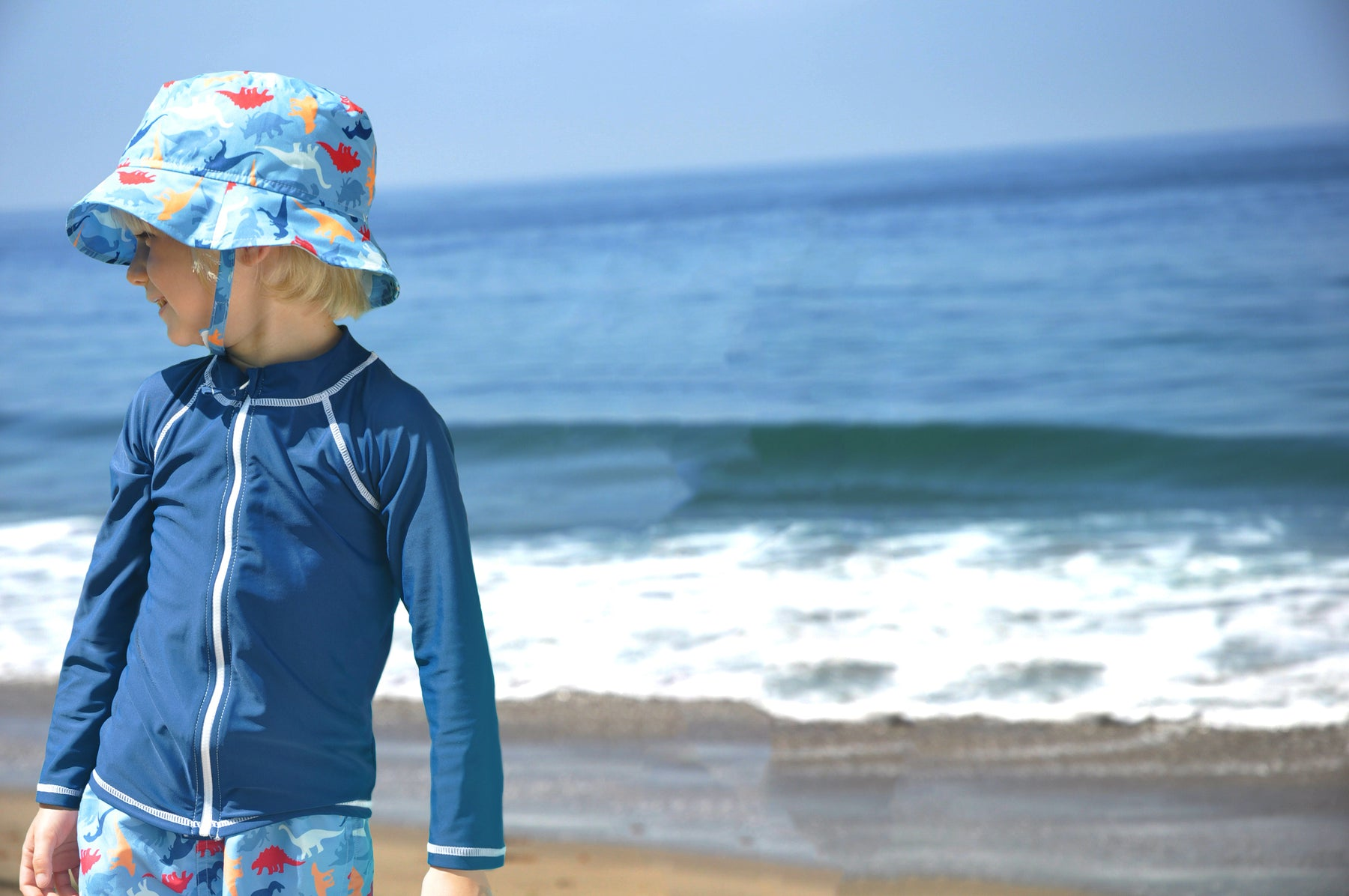 Young boy is standing at the beach in front of the ocean looking off to the left. Boy wearing matching blue dinosaur print Flap Happy bucket hat and shorts with blue front zip rash guard.