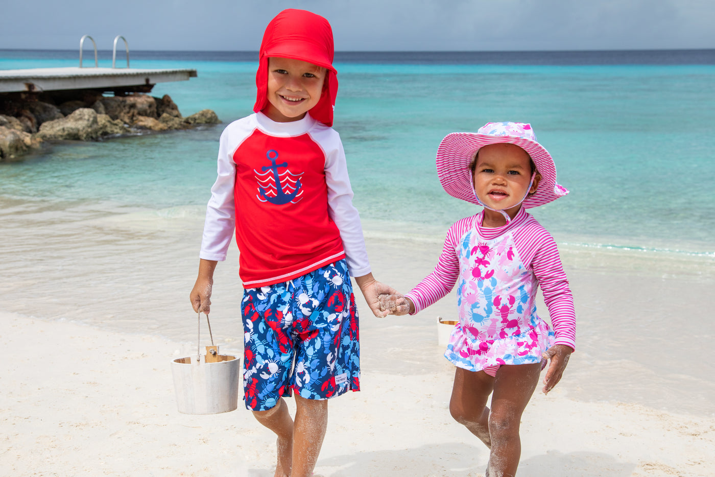 Toddler boy holding hands with infant girl walking on the beack happily wearing flap happy swim hats and matching swimwear.