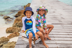 Boy and girl wearing flap happy hats and swimwear happily sitting on the pier at the beach.