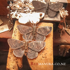 Jewellery nz | Purere Parangunu Peacock Moth Silver Brooch and necklace on bench peg