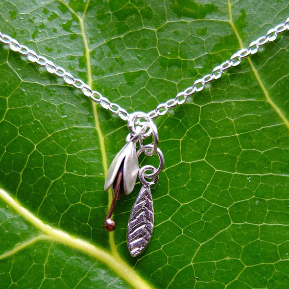 SIlver Bud and Leaf necklace. Small flower hangs over a silver leaf, by NZ jeweller Martyn Milligan, Rinopai, Golden Bay , Nelson.