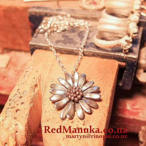 Jewellery NZ | Daisy Necklace | Redmanuka with chain on bench peg