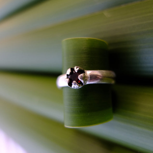 Red Mānuka Ring sitting on a puka leaf | nz jewellery | Redmānuka sitting on a