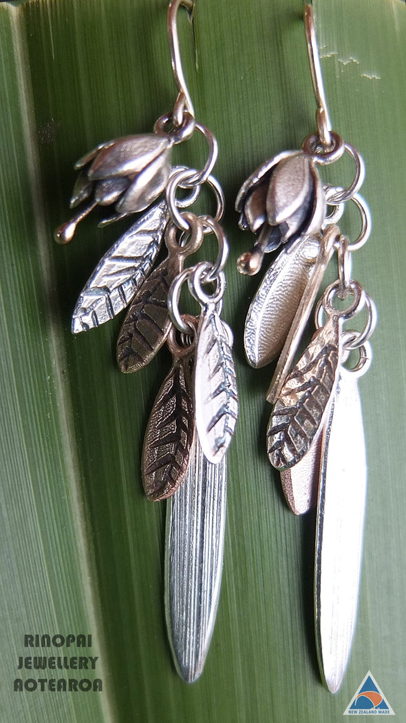 Springs Promise Gold and Silver Earrings, shown on a harakeke leaf by jewellery nz designer Martyn Milligan