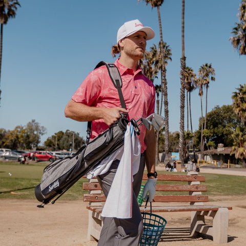 a man walking with his golf towel hanging from his golf bag