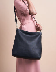 Black Leather shopper bag. Square shape with an adjustable and removable strap. Model product image.
