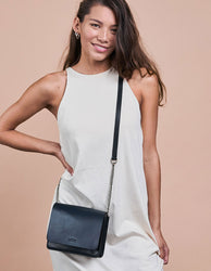 Navy & Black Leather womens handbag. Square shape with a chain strap. Model product image