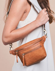 Cognac Leather womens fanny pack. Square shape with an adjustable strap. Model product image