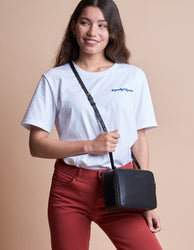 Black Leather womens crossbody bag. Square shape with an adjustable strap. Model product image