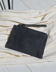 Small Black Hunter Leather coin purse. Square shape. Lifestyle image