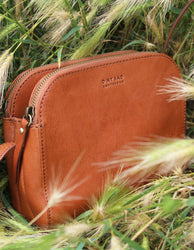Cognac Leather womens handbag. Square shape with an adjustable strap. Lifestyle image.