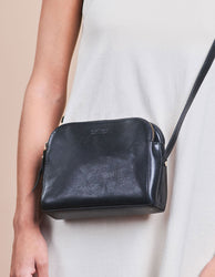 Black Leather womens handbag. Square shape with an adjustable strap. Model image.