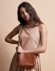 Cognac Leather womens handbag. Square shape with an adjustable strap. Model image.