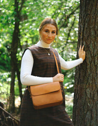 Cognac Leather womens handbag. Square shape with an adjustable strap. Lifestyle product image.