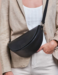 Laura Bag Black Classic Leather. Round mood shape crossbody bag for women. Model image.
