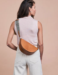 Laura Bag Cognac Classic Leather. Round mood shape crossbody bag for women. Model image.