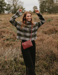 Lola Ruby Classic Leather. Small Rectangular crossbody clutch bag for women with two zipper compartments. Model image.