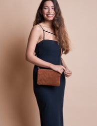 Lola Wild Oak Soft Grain Leather. Small Rectangular crossbody clutch bag for women with two zipper compartments. Model image.