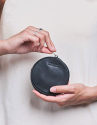 Luna Purse Black Soft Grain Leather. Circular coin purse, wallet for men and women. Model image.
