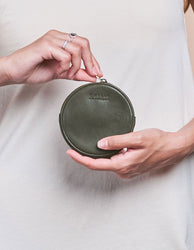 Luna Purse Green Soft Grain Leather. Circular coin purse, wallet for men and women. Model image.