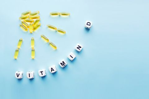 Yellow capsules forming a sun shape with the word vitamin D spelled out on white cubes over a blue background
