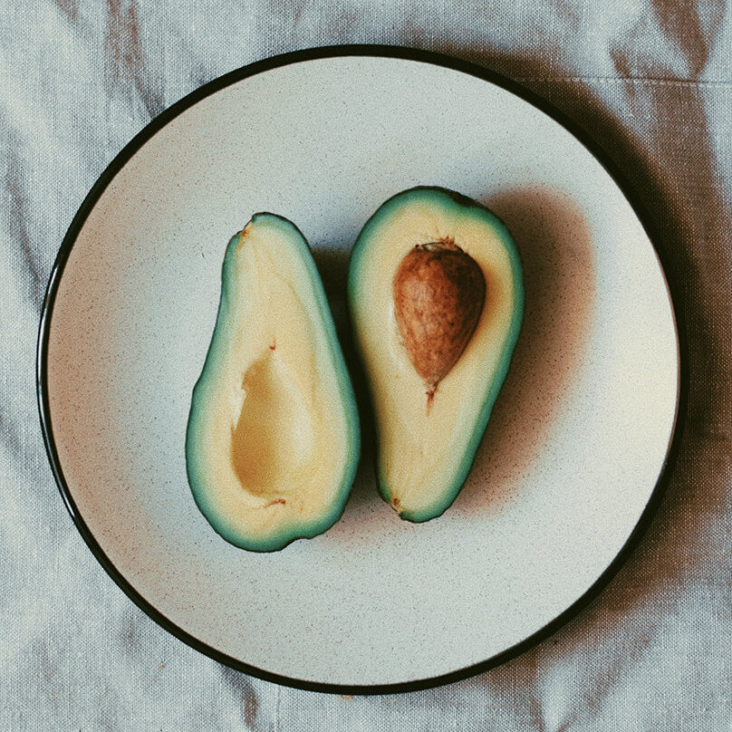Potassium pictured as an avocado cut in two pieces on a circular plate