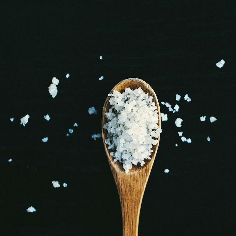 Sodium pictured as crystals in a wooden spoon