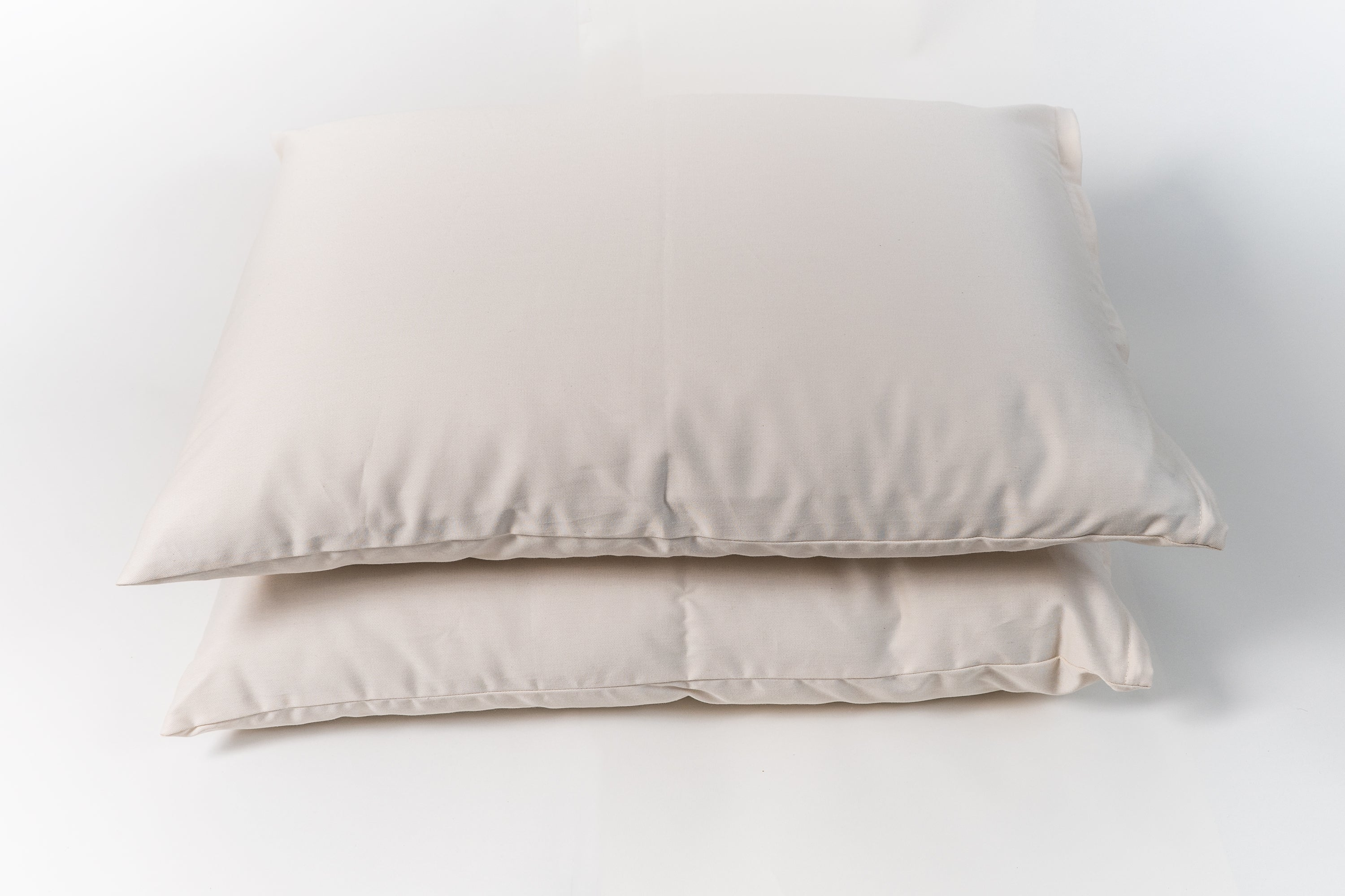 Natural wooly bolas pillow. Covered in a sateen fabric of organic cotton fibers.