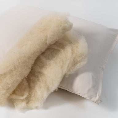 Natural wool pillow. Covered in a sateen fabric of organic cotton fibers.