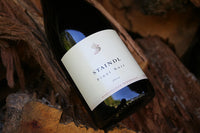 A bottle of Staindl Wines 2012 Pinot Noir rests on the bark of a log