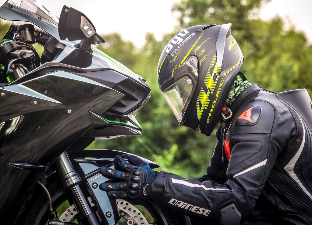 Man wearing a motorbike helmet looking at a bike