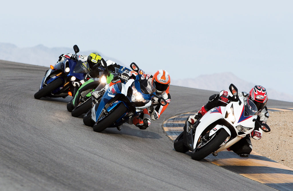 Motorcycle racers making a corner wearing motorbike helmets